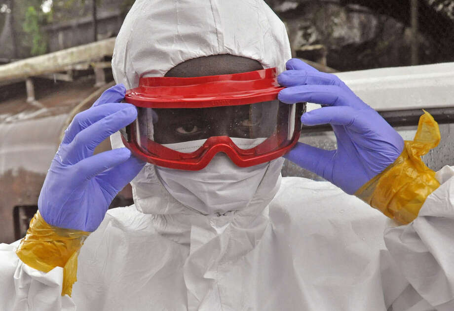 A Liberian health worker prepare his Ebola protective gear before removing the body of a man that they believe died from the Ebola virus in Monrovia, Liberia, Friday, Aug. 29, 2014. The Ebola outbreak in West Africa eventually could exceed 20,000 cases, more than six times as many as are now known, the World Health Organization said Thursday. A new plan released by the U.N. health agency to stop Ebola also assumes that the actual number of cases in many hard-hit areas may be two to four times higher than currently reported.(AP Photo/Abbas Dulleh)