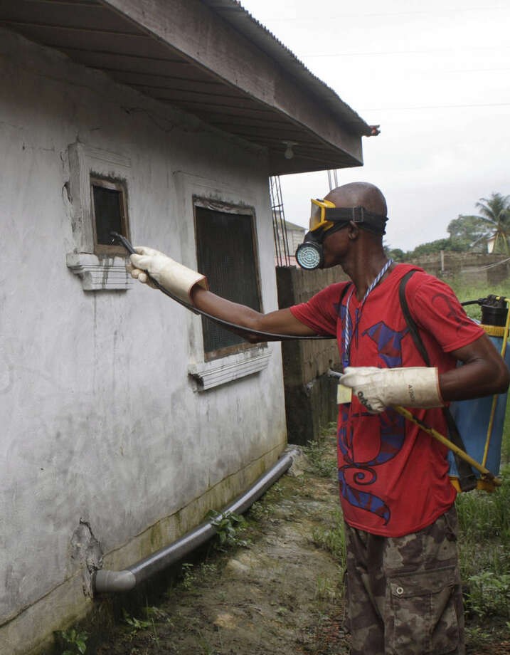 A man that was hired by the community sprays chemicals to try and prevent the spread of the Ebola virus is seen in Monrovia, Liberia, Friday, Aug. 29, 2014. The Ebola outbreak in West Africa eventually could exceed 20,000 cases, more than six times as many as are now known, the World Health Organization said Thursday. A new plan released by the U.N. health agency to stop Ebola also assumes that the actual number of cases in many hard-hit areas may be two to four times higher than currently reported.(AP Photo/Abbas Dulleh)