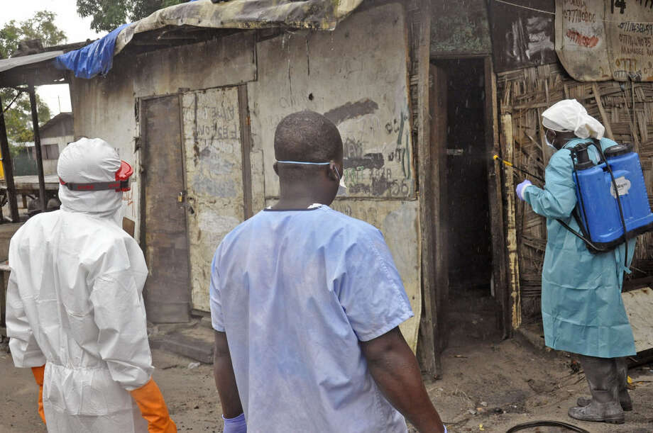 Liberian health workers spray disinfectant outside a house before entering and removing the body of a man that they believe died from the Ebola virus in Monrovia, Liberia, Friday, Aug. 29, 2014. The Ebola outbreak in West Africa eventually could exceed 20,000 cases, more than six times as many as are now known, the World Health Organization said Thursday. A new plan released by the U.N. health agency to stop Ebola also assumes that the actual number of cases in many hard-hit areas may be two to four times higher than currently reported.(AP Photo/Abbas Dulleh)