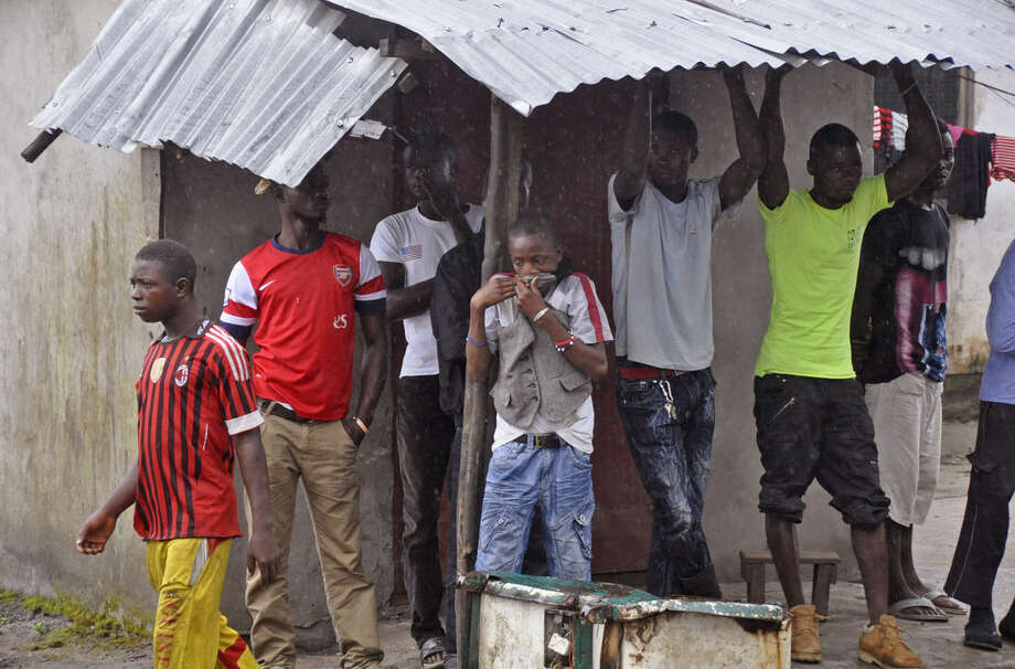 AP photoFamily members and friends of a man believed to have died form the Ebola virus, gather near his home as his body is removed by health workers in Monrovia, Liberia on Friday.
