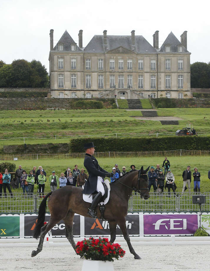 Michael Jung of Germany, riding Fischerrocana during the first day of the dressage test of the Eventing competition at the FEI World Equestrian Games, at the French National Stud, in Le Pin-au-Haras, western France, Thursday, Aug. 28, 2014. Chateau du Haras du Pin in the background. (AP Photo/Michel Euler)