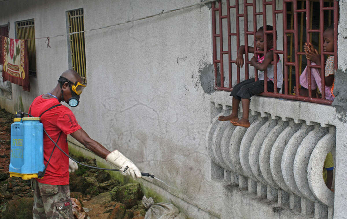 A man that was hired by the community sprays chemicals to try and prevent the spread of the Ebola virus, as local children look on, in Monrovia, Liberia, Friday, Aug. 29, 2014. The Ebola outbreak in West Africa eventually could exceed 20,000 cases, more than six times as many as are now known, the World Health Organization said Thursday. A new plan released by the U.N. health agency to stop Ebola also assumes that the actual number of cases in many hard-hit areas may be two to four times higher than currently reported.(AP Photo/Abbas Dulleh)