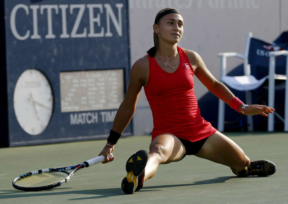 Aleksandra Krunic, of Serbia, slides on the court as she watches her shot fall against Madison Keys, of the United States, during the second round of the 2014 U.S. Open tennis tournament, Thursday, Aug. 28, 2014, in New York. (AP Photo/Frank Franklin)