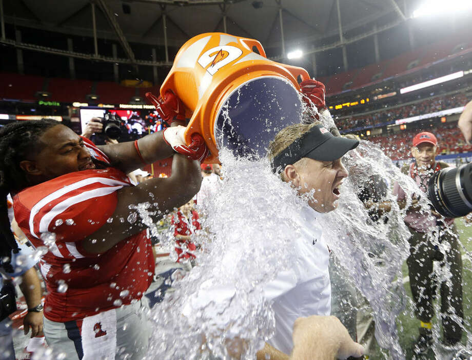 Mississippi coach Hugh Freeze gets dunked by Mississippi offensive linesman Justin Bell after Mississippi defeated Boise State 35-13 in an NCAA college football game Thursday, Aug. 28, 2014, in Atlanta. (AP Photo/John Bazemore)