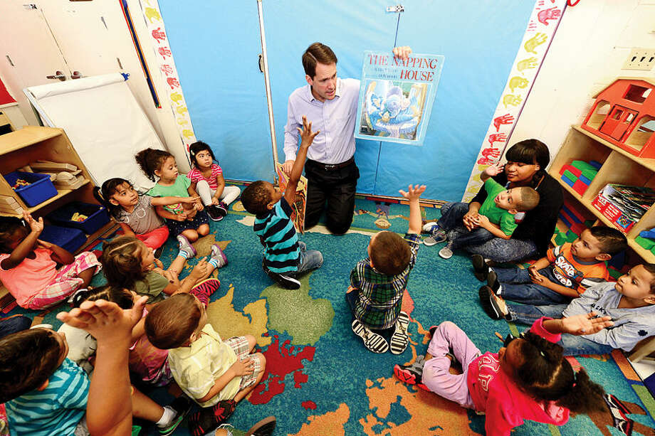 Hour photo / Erik Trautmann US Congressman Jim Himes reads a book to Laticha Barnes' class as he tours the Head Start program at Nathaniel Ely Elementary School to discuss his advocacy for Head Start and early education programs Friday morning.