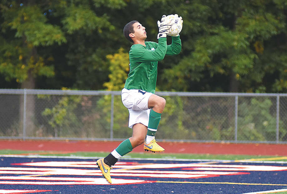Hour photo/John Nash - Staples goalkeeper Noah Schwaeber makes a leaping save during Wednesday's game against Brien McMahon.
