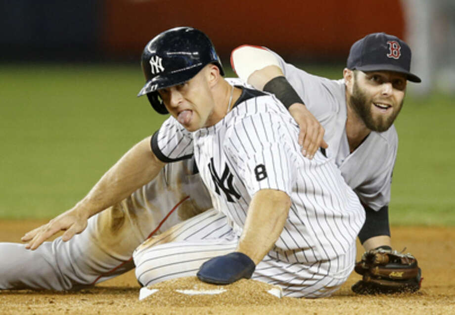 Boston Red Sox second baseman Dustin Pedroia, right, looks from behind New York Yankees Brett Gardner after putting Gardner out when New York Yankees designated hitter Alex Rodriguez hit into a fifth-inning double play in a baseball game in New York, Tuesday, Sept. 29, 2015. (AP Photo/Kathy Willens)