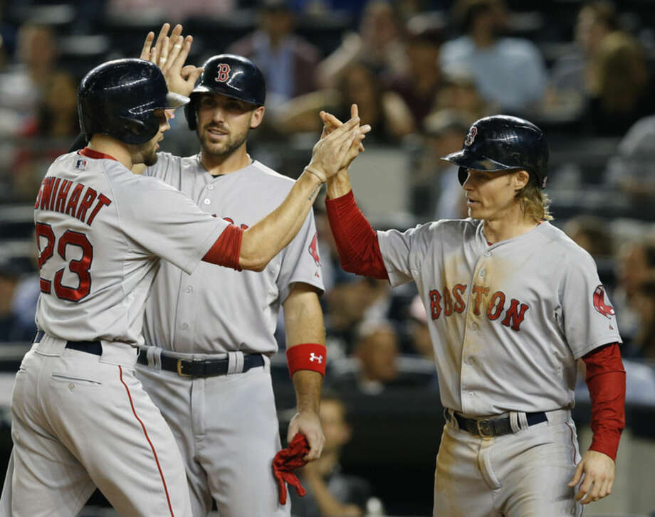 Boston Red Sox Travis Shaw, center, and Brock Holt greet Blake Swihart (23) after they scored on Swihart's first-inning three-run home run in a baseball game against the New York Yankees in New York, Tuesday, Sept. 29, 2015. (AP Photo/Kathy Willens)