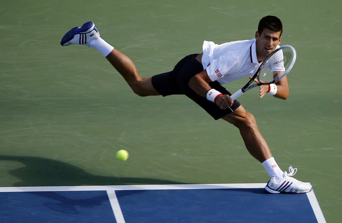 Novak Djokovic, of Serbia, returns a shot to Paul-Henri Mathieu, of France, during the second round of the 2014 U.S. Open tennis tournament, Thursday, Aug. 28, 2014, in New York. (AP Photo/Elise Amendola)