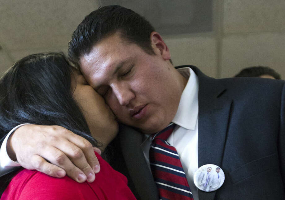 David Barajas gets a kiss from his wife Cindy after a jury acquitted him of murder at the Brazoria County Courthouse on Wednesday, Aug. 27, 2014, Angleton, Texas. Barajas was accused of fatally shooting Jose Banda in December 2012 near Alvin, minutes after Banda hit a truck Barajas and his two sons were pushing after it ran out of gas. Twelve-year-old David Jr. and 11-year-old Caleb were killed. He could have been sentenced to up to life in prison, if he had been convicted. (AP Photo/Patric Schneider)