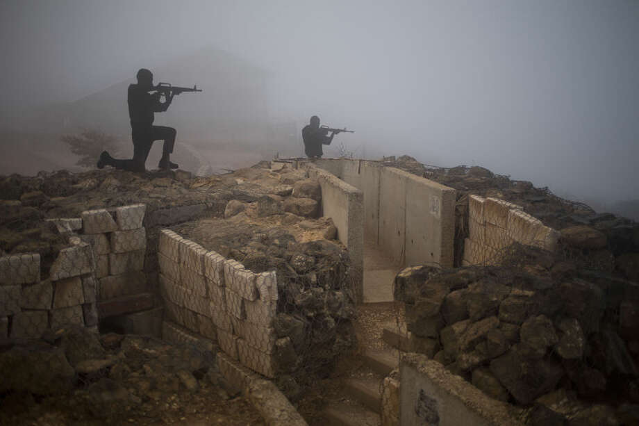 """Metal boards in the shape of gunmen sit on an old bunker at an observation point on Mt. Bental in the Israeli controlled Golan Heights, overlooking the border with Syria near the Quneitra province, Friday, Aug. 29, 2014. An armed group detained more than 40 U.N. peacekeepers during fighting in Syria early Thursday and over 80 peacekeepers are trapped, the United Nations said. The peacekeepers were detained on the Syrian side of the Golan Heights during a """"period of increased fighting between armed elements and the Syrian Arab Armed Forces,"""" the office of U.N. Secretary-General Ban Ki-moon said in a statement. ( AP Photo/Ariel Schalit)"""