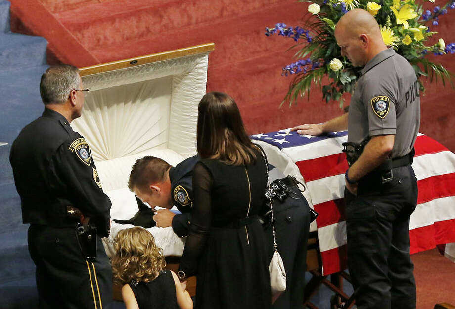 Oklahoma City police officer Sgt. Ryan Stark, center, leans over the casket of his canine partner, K-9 Kye, following funeral services for the dog in Oklahoma City, Thursday, Aug. 28, 2014. K-9 Kye, a three year old Belgian German Shepard, died Aug. 25 after being stabbed by a burglary suspect on Aug. 24. Sgt. Stark tried to separate the dog and the suspect before fatally shooting the suspect. (AP Photo/Sue Ogrocki)
