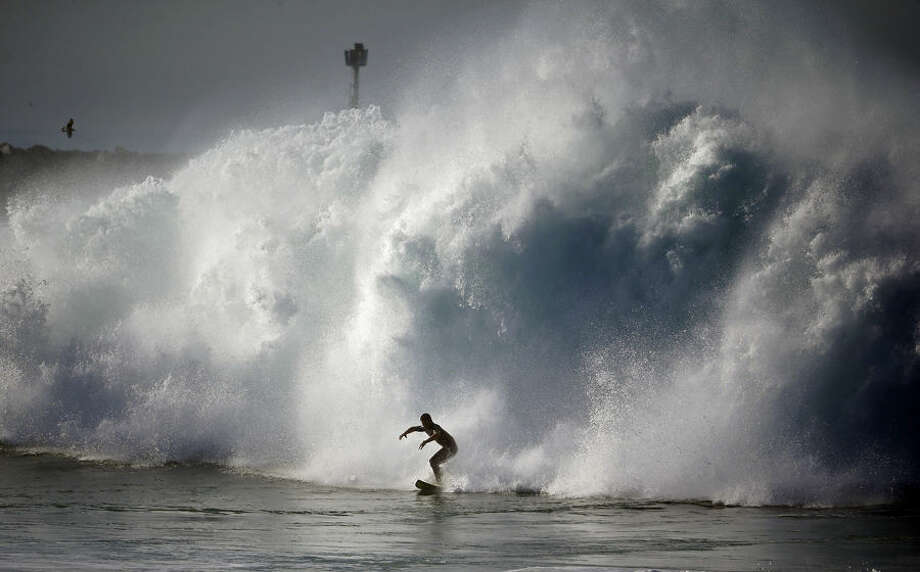 A surfer rides a wave at the wedge in Newport Beach, Calif., Wednesday, Aug. 27, 2014. Southern California beachgoers experienced much higher than normal surf, brought on by Hurricane Marie spinning off the coast of Mexico. (AP Photo/Chris Carlson)
