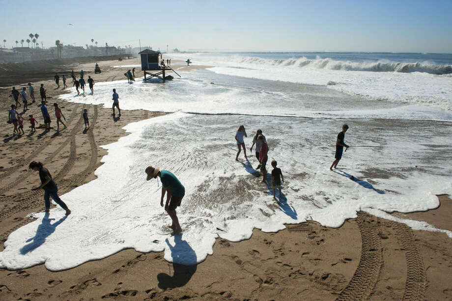 Spectators on the beach scramble as a wave covers the beach as huge swells from Hurricane Marie in the Pacific Ocean west of Mexico caused unexpected flooding at the oceanfront in Seal Beach, Calif. on Wednesday, Aug. 27, 2014. (AP Photo/The Orange County Register, Ken Steinhardt)