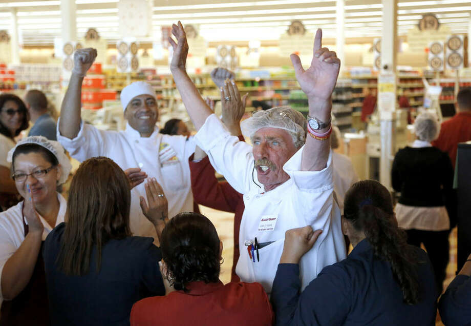 Market Basket meat manager Bob Dietz, of Methuen, Mass., center, raises his arms in celebration after watching a televised speech by restored Market Basket CEO Arthur T. Demoulas at a store location, Thursday, Aug. 28, 2014, in Chelsea. A six-week standoff between thousands of employees of the New England supermarket chain and management has ended with the news that beloved former CEO Demoulas is back in control after buying the entire company. Demoulas made his speech to workers in Tewksbury, Mass. (AP Photo/Steven Senne)