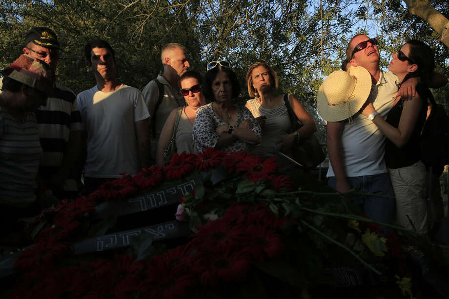 Friends and relatives mourn during the funeral of Ze'evik Etzion, a 55 year old security officer who was killed two days ago by Palestinian mortar shell in Kibbutz Nirim near the Israel Gaza border, Thursday, Aug. 28, 2014. (AP Photo/Tsafrir Abayov)
