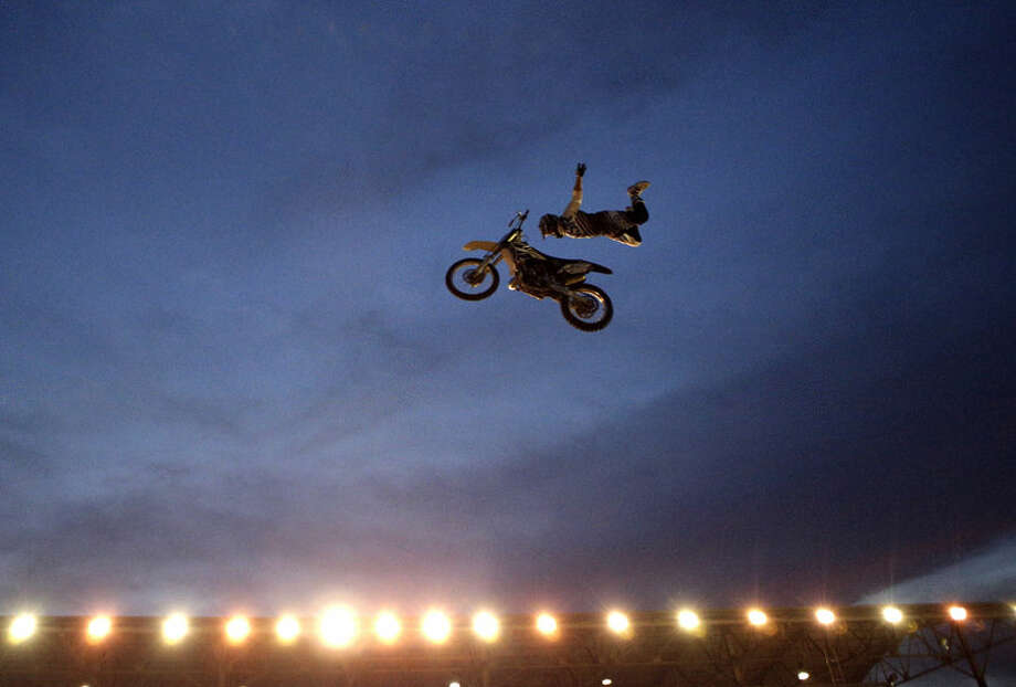 Eric Farr of Grand Junction, Colo. performs with his motorcycle during the U.S. FMX Motorcross Championship Series event at the Stark County Fair in Canton, Ohio on Wednesday, Aug. 27, 2014. (AP Photo/The Repository, Bob Rossiter)