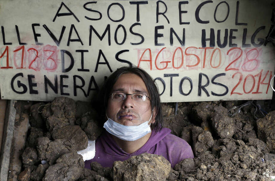 Jorge Alberto Parra lies partially buried in the ground with his lips sewn shut, on the sidewalk area outside the U.S. embassy in Bogota, Colombia, Thursday, Aug. 28, 2014. Parra and three other men said they are protesting the General Motors Company (GM) for being unfairly laid-off three years ago. Parra partially buried himself today. (AP Photo/Fernando Vergara)