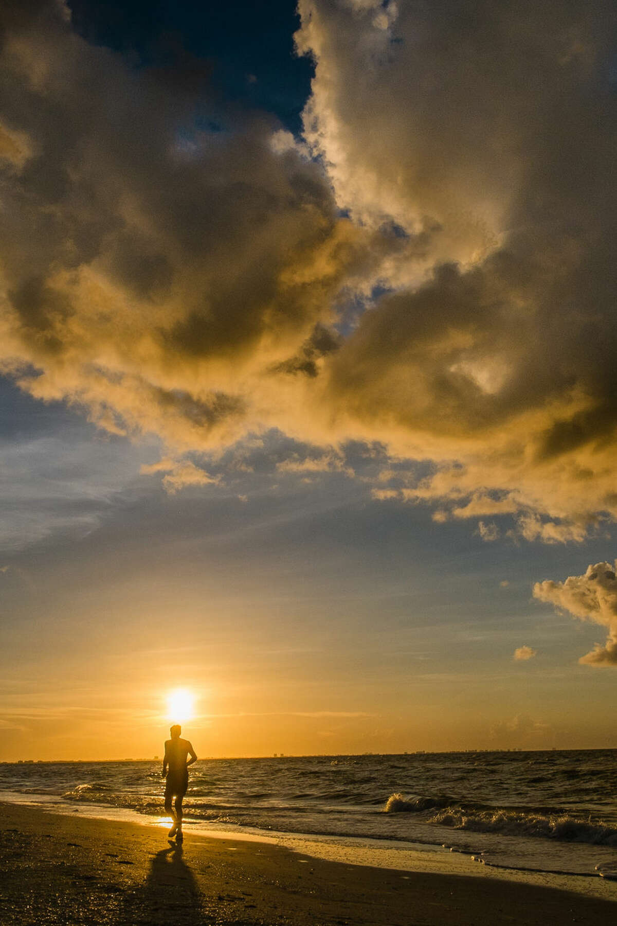 A jogger runs along the Sanibel Island, Fla. beach at daybreak in the waning days of summer Friday, Aug. 29, 2014. (AP Photo/J. David Ake)