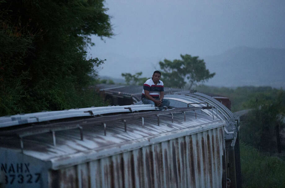 "In this Aug. 26, 2014 photo, a Central American migrant sits alone atop a freight train as it heads north from Arriaga to Ixtepec, Mexico. A Mexican crackdown seems to be keeping women and children off the deadly train, known as ""The Beast,"" that has traditionally helped thousands of migrants head north. The once-open route to the United States has become so difficult that trains now carry a small fraction of the migrants they used to, and almost exclusively adult men. (AP Photo/Rebecca Blackwell)"