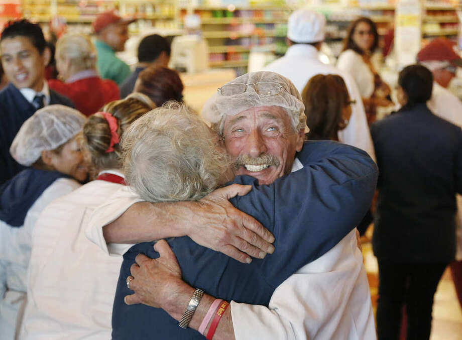 Market Basket meat manager Bob Dietz, of Methuen, Mass., front right, hugs cashier Mary Olson, of Chelsea, Mass., after watching a televised speech by restored Market Basket CEO Arthur T. Demoulas at a store location, Thursday, Aug. 28, 2014, in Chelsea. A six-week standoff between thousands of employees of the New England supermarket chain and management has ended with the news that the beloved Demoulas is back in control after buying the entire company. Demoulas made his speech to workers in Tewksbury, Mass. (AP Photo/Steven Senne)