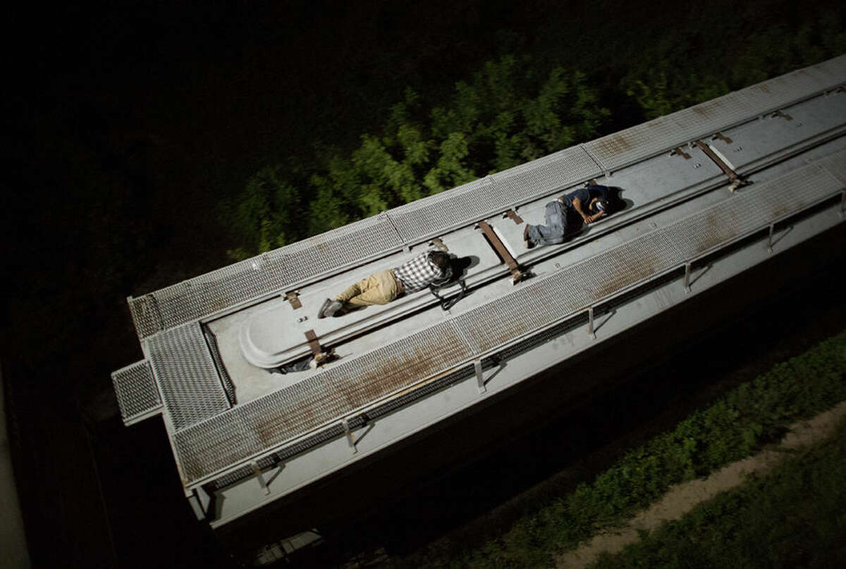 In this Aug. 26, 2014 photo, Central American migrants sleep atop a moving freight train as it heads north from Arriaga toward Chahuites, Mexico. A Mexican crackdown seems to be keeping women and children off the deadly train, known as