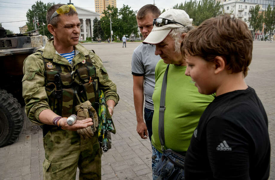 """A Pro-Russian rebel shows the people a grenade as he patrols Lenin square in the town of Donetsk, eastern Ukraine, Thursday, Aug. 28, 2014. Ukraine's president Petro Poroshenko called an emergency meeting of the nation's security council and canceled a foreign trip Thursday, declaring that """"Russian forces have entered Ukraine,"""" as concerns grew about the opening of a new front in the conflict. (AP Photo/Mstislav Chernov)"""