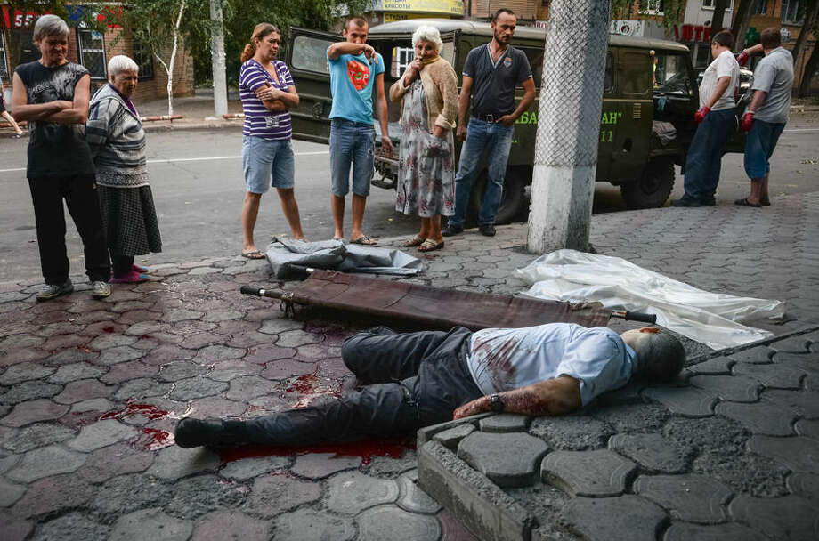 """EDS NOTE GRAPHIC CONTENT: People look at the dead body of man killed by shelling in the town of Donetsk, eastern Ukraine, Thursday, Aug. 28, 2014. Ukraine's president Petro Poroshenko called an emergency meeting of the nation's security council and canceled a foreign trip Thursday, declaring that """"Russian forces have entered Ukraine,"""" as concerns grew about the opening of a new front in the conflict. (AP Photo/Mstislav Chernov)"""