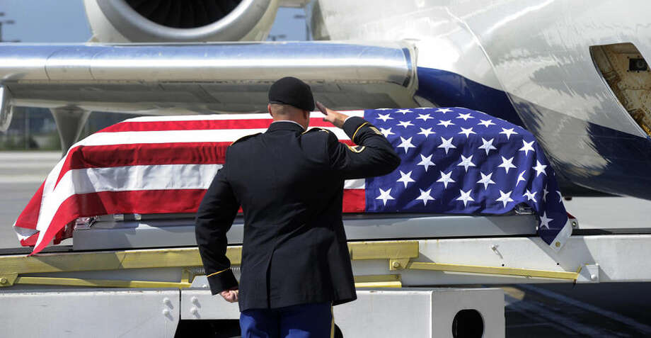 Honors are rendered as the remains of U.S. Army Pfc. Cecil Harris arrive at McGhee Tyson Airport in Knoxville, Tenn. on Wednesday, Aug. 27, 2014. On Jan. 2, 1945, 19-year-old Harris went missing while serving with the 45th Infantry Division during World War II. His remains were returned home after a hiker found his burial site last year near Dambach, France. He will be buried at Arlington National Cemetery. (AP Photo/Knoxville News Sentinel, Michael Patrick)