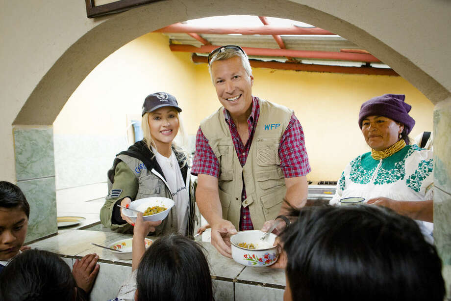 This Sept. 22, 2015 photo released by Yum! Brands shows singer Christina Aguilera, left, and Jonathan Blum, Chief Public Affairs Officer of Yum! Brands, serving food to children in Ecuador through the United Nations World Food Programme's (WFP) school feeding program. Aguilera was on a humanitarian trip in Ecuador last week filming a new PSA for Yum! Brands World Hunger Relief effort that raises awareness, volunteerism and funds for WFP and other hunger relief agencies. (Robb Dipple/Hilton Media Group via AP)