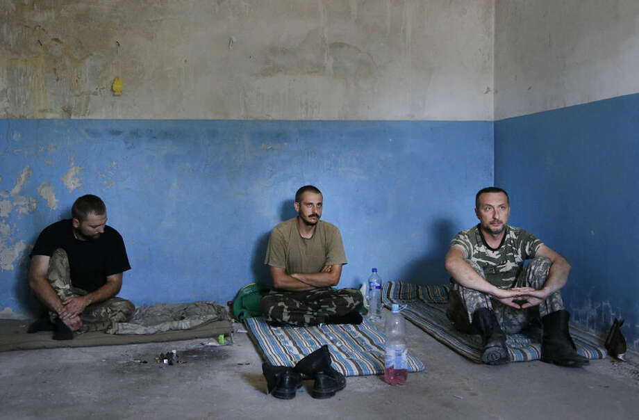 Captured Ukrainian border guards sit in a garage at the Novoazovsk border crossing point, in eastern Ukraine, Friday, Aug. 29, 2014. At Novoazovsk, rebel fighters looked to be in firm control, well-equipped and relaxed. At least half a dozen tanks were seen on roads around the town, although the total number at the rebels' disposal is believed to be much greater. Novoazovsk fell swiftly to the rebels Wednesday after being pounded by shelling.(AP Photo/Sergei Grits)