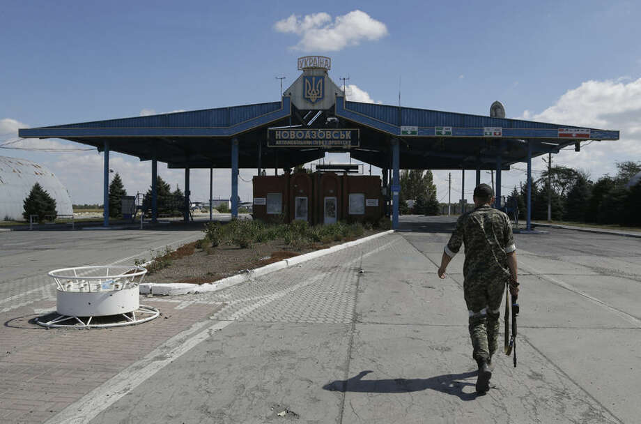 A Pro-Russian rebel walks at the Novoazovsk border crossing point, in eastern Ukraine, Friday, Aug. 29, 2014. In Novoazovsk, pro Russian rebel fighters looked to be in firm control, well-equipped and relaxed. At least half a dozen tanks were seen on roads around the town, although the total number at the rebels' disposal is believed to be much greater. Novoazovsk fell swiftly to the rebels Wednesday after being pounded by shelling.(AP Photo/Sergei Grits)