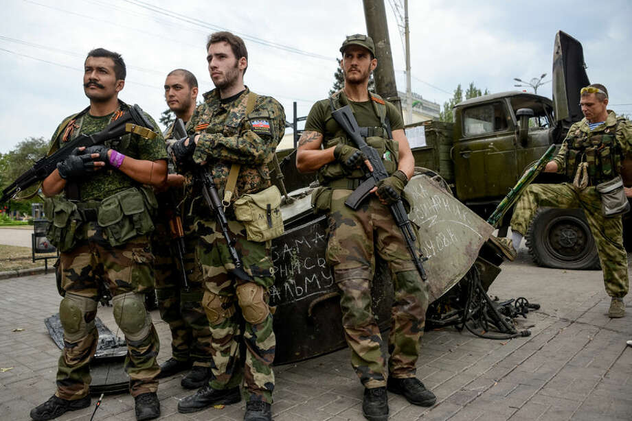 """French volunteers, supporters of Pro-Russian rebels, stands near destroyed Ukrainian military machines at the Lenin square in the town of Donetsk, eastern Ukraine, Thursday, Aug. 28, 2014. Ukraine's president Petro Poroshenko called an emergency meeting of the nation's security council and canceled a foreign trip Thursday, declaring that """"Russian forces have entered Ukraine,"""" as concerns grew about the opening of a new front in the conflict. (AP Photo/Mstislav Chernov)"""