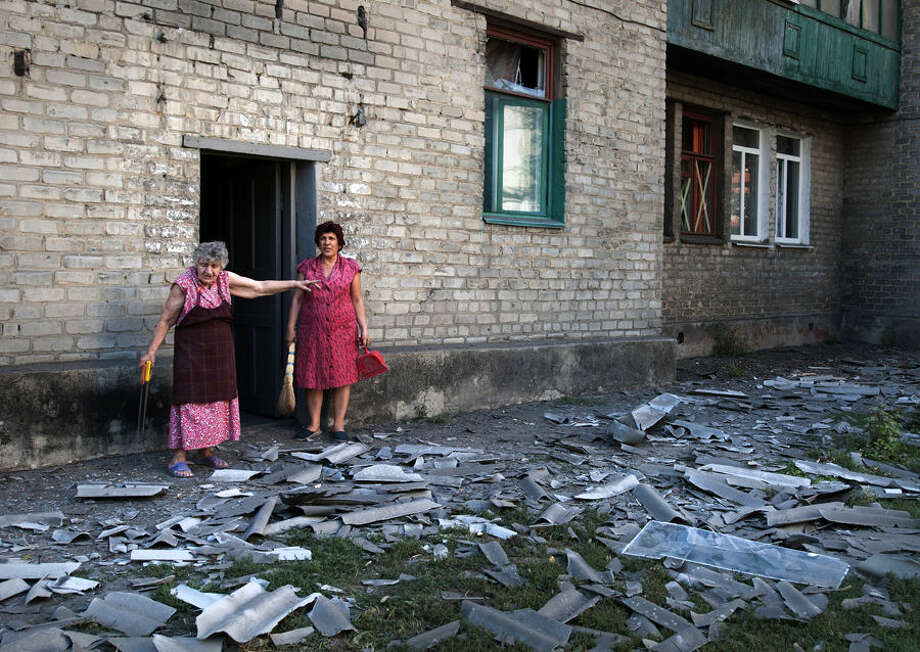 In this photo taken Wednesday, Aug. 27, 2014, local residents stand near the building where they live after a shelling in Donetsk, eastern Ukraine. Two columns of Russian tanks and military vehicles fired Grad missiles at a border post in southeastern Ukraine, then rolled into the country Thursday as Ukraine's overmatched border guards fled, a top Ukrainian official said. (AP Photo/Antoine E.R. Delaunay)