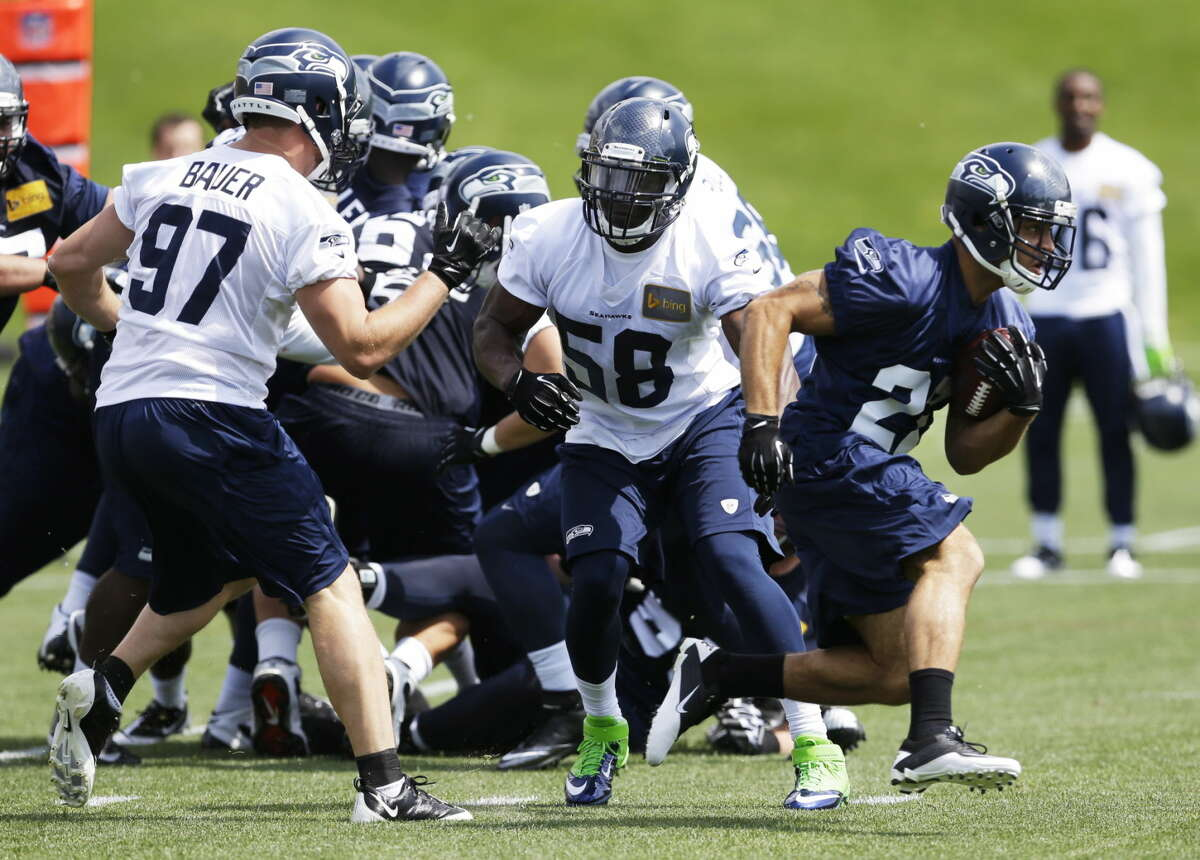 Seattle Seahawks rookie running back Dillon Baxter, right, runs through the defense of rookie defensive end Cody Bauer (97) and rookie linebacker Kevin Pierre-Louis (58), Friday, May 16, 2014, during an NFL football rookie minicamp in Renton, Wash. (AP Photo/Ted S. Warren)