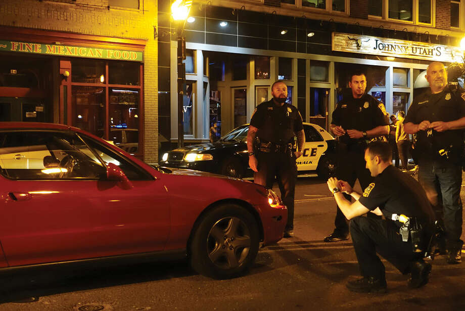Hour photo/Jeff Dale Norwalk police investigate a hit and run with a pedestrian Thursday night on Washington Street.