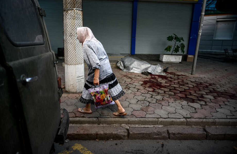 "An elderly woman passes by dead body of man killed by shelling in the town of Donetsk, eastern Ukraine, Thursday, Aug. 28, 2014. Ukraine's president Petro Poroshenko called an emergency meeting of the nation's security council and canceled a foreign trip Thursday, declaring that ""Russian forces have entered Ukraine,"" as concerns grew about the opening of a new front in the conflict. (AP Photo/Mstislav Chernov)"