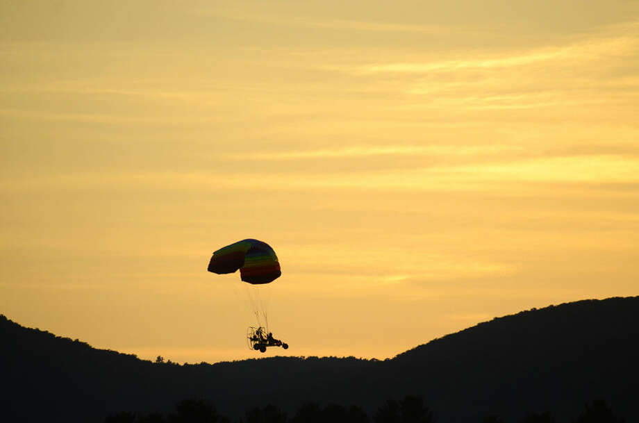 An ultralight aricraft flys over the Berkshire mountains surrounding Pittsfield, Mass., Tuesday Aug 25, 2014 at dusk. (AP Photo The Berkshire Eagle/Ben Garver)