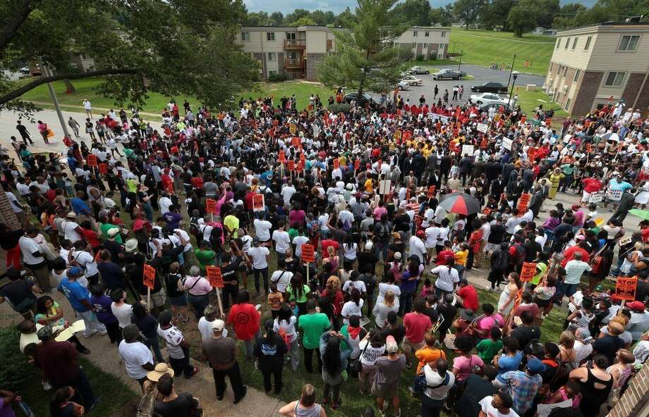 Hundreds of people gather at the Canfield Green apartments for prayer around the memorial to Michael Brown, an unarmed black 18-year-old who was fatally shot by a white police officer three weeks earlier, during a rally in Ferguson, Mo. on Saturday, Aug. 30, 2014. (AP Photo/St. Louis Post-Dispatch, Robert Cohen)