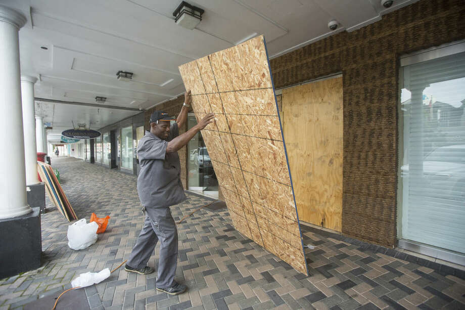 Perry Williams, 47, puts up plywood shutters to cover the windows of the Diamond's International store, in preparation for the arrival of hurricane Joaquin, in Nassau, Bahamas, Thursday, Oct. 1, 2015. Joaquin unleashed heavy flooding as it roared through sparsely populated islands in the eastern Bahamas as a Category 4 storm, with forecasters warning it could grow even stronger before carving a path that would take it near the U.S. East Coast. (AP Photo/Tim Aylen)
