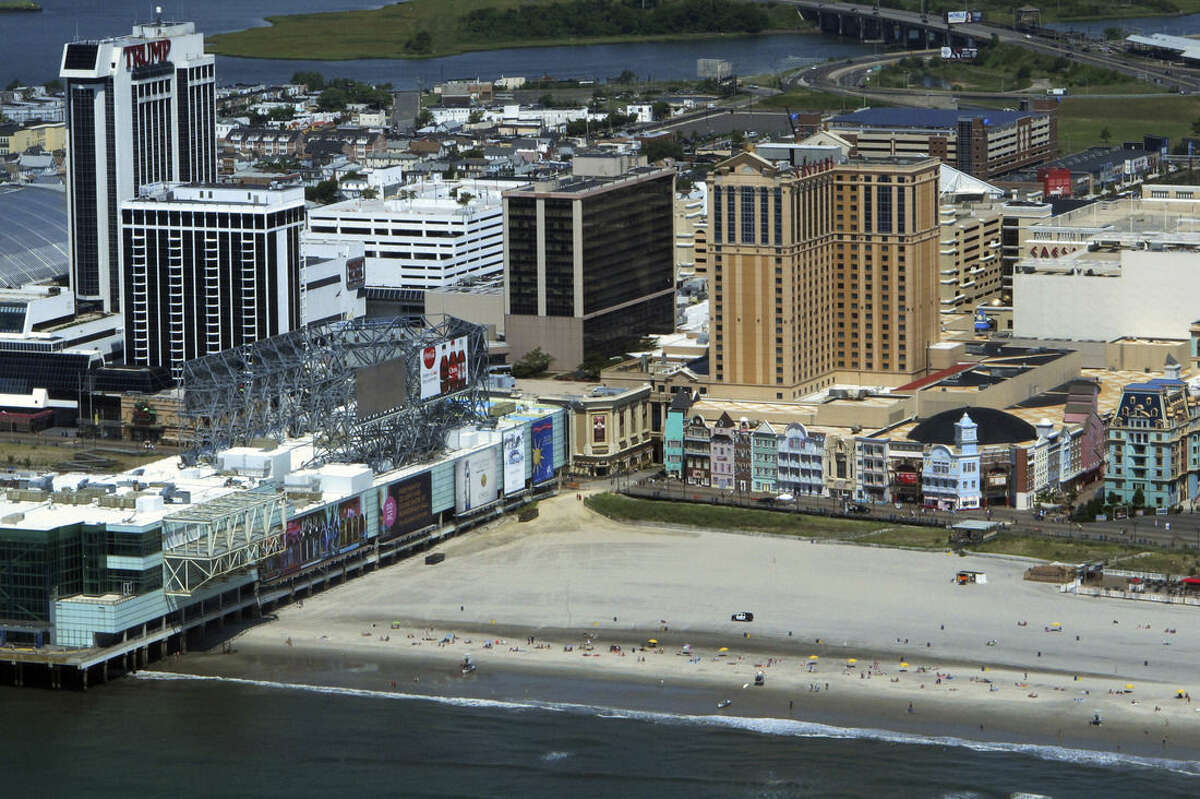 This July 11, 2014 aerial photo shows Trump Plaza, left, and Caesars Atlantic City, right, on the Atantic City N.J. Boardwalk. A report issued Aug. 29, 2014 by Wall Street firm Fitch Ratings predicts much of the gambling revenue from Trump Plaza and two other casinos closing down soon, Revel and the Showboat, will remain in Atlantic City after they are gone. (AP Photo/Wayne Parry)