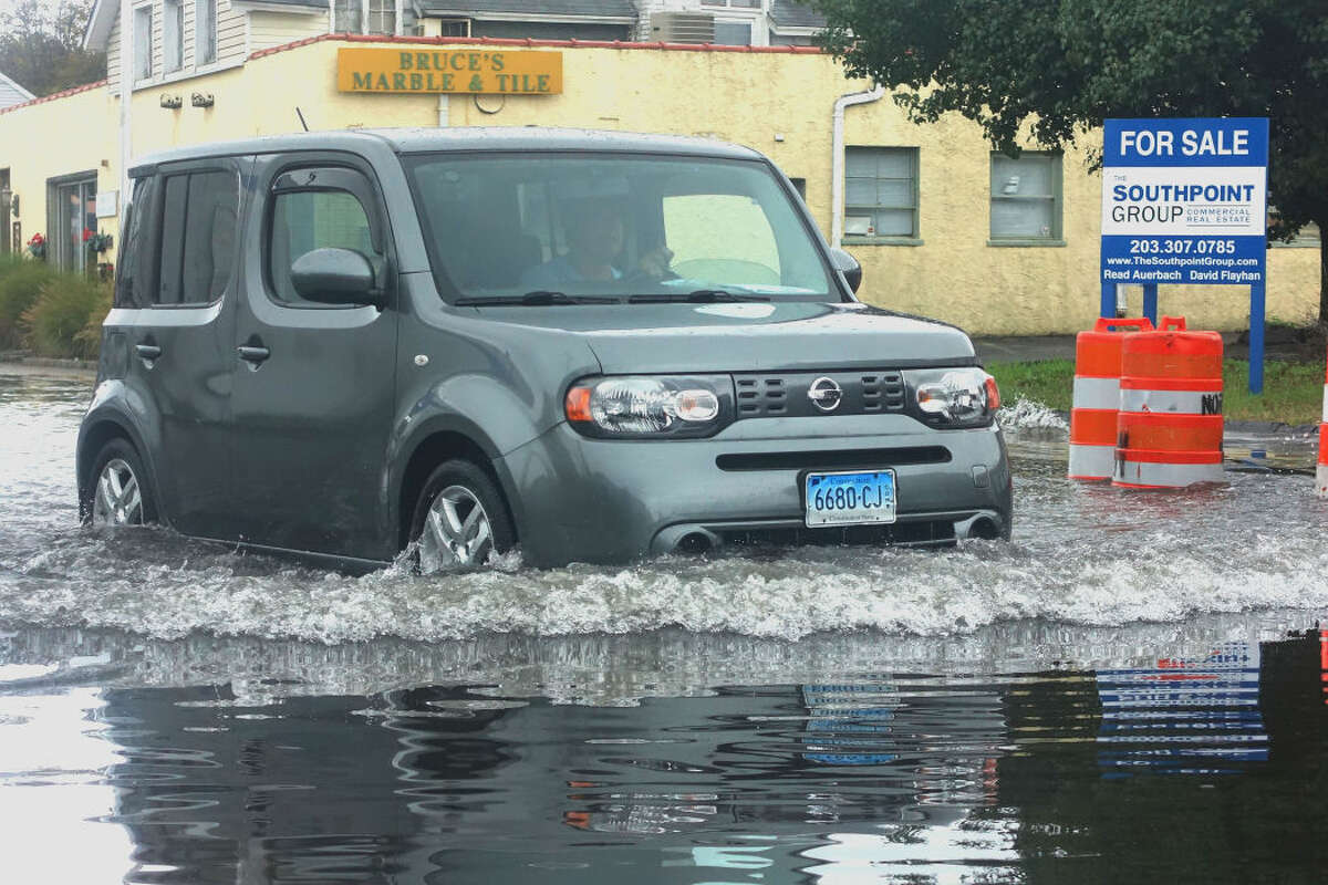 Hour photo/Jeff Dale Driver Joe Mallozzi slowly traverses his Scion Cube through a large puddle on Water Street in SoNo Wednesday after heavy rain overnight. Water Street from Hanford Place to Concord Street was closed as a result of the flooding.