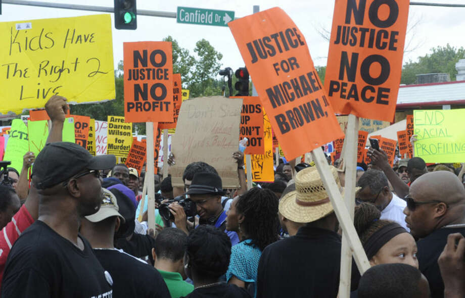 Demonstrators gather for a rally in Ferguson, Mo. on Saturday, Aug. 30, 2014 near the site where Michael Brown, an unarmed black 18-year-old, was fatally shot by a white police officer three weeks earlier. (AP Photo/Bill Boyce)
