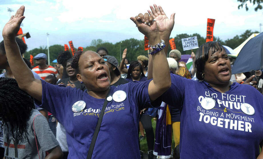 AP photo/Bill BoyceSharon Garner, right, and Regina Hamm of St. Louis participate in a rally in Ferguson, Mo. on Saturday near the site where Michael Brown, an unarmed black 18-year-old, was fatally shot by a white police officer three weeks earlier.