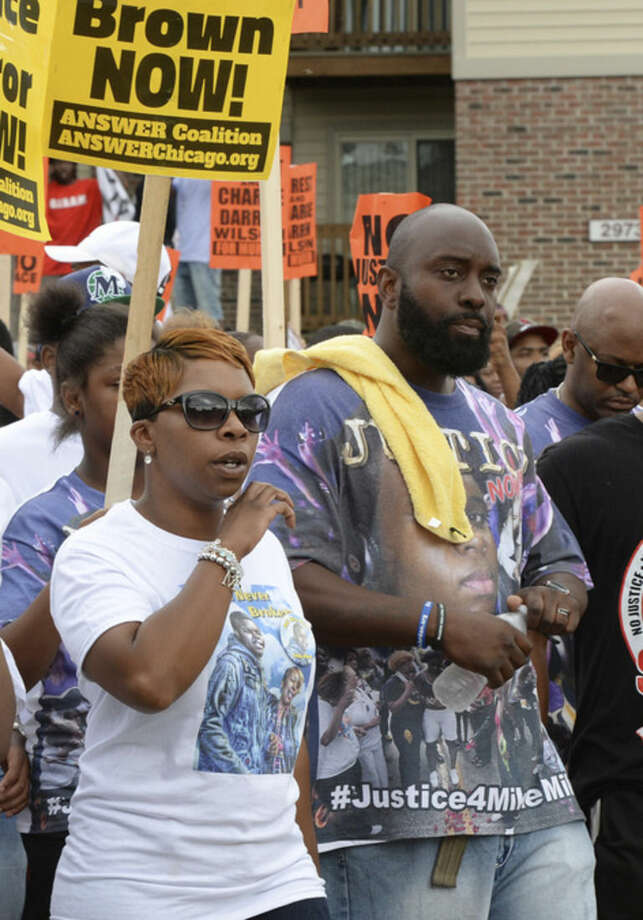 Parents of Michael Brown, Lesley McSpadden, left, and Michael Brown, Sr., lead a rally in Ferguson, Mo. on Saturday, Aug. 30, 2014 near the site where Michael, an unarmed black 18-year-old, was fatally shot by a white police officer three weeks earlier. (AP Photo/Bill Boyce)