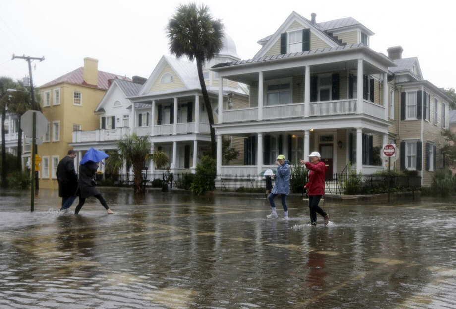 People cross a flooded street in Charleston, S.C., Saturday, Oct. 3, 2015. A flash flood warning was in effect in parts of South Carolina, where authorities shut down the Charleston peninsula to motorists. (AP Photo/Chuck Burton)