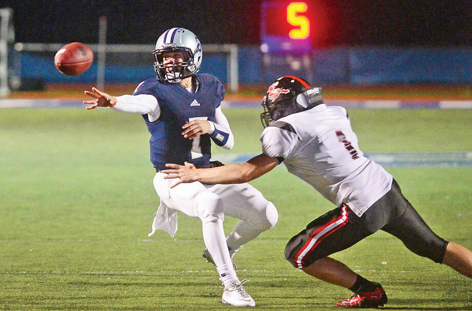 Staples quarterback Andrew Speed pitches the ball as the Wreckers battle Fairfield Warde Friday night in Westport. Staples won, 35-15. (Hour photo/Erik Trautmann)