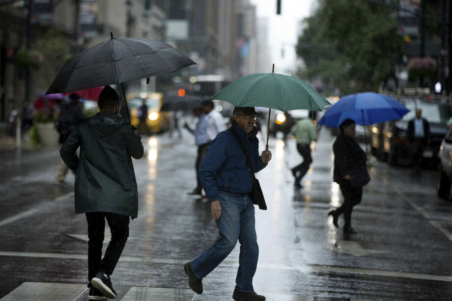 Pedestrians negotiate rainy conditions along Lexington Avenue Friday, Oct. 2, 2015, in New York. Rainfall and heavy winds are expected to last through the weekend. (AP Photo/Kevin Hagen)