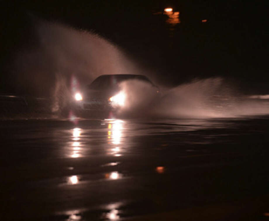 A car splashes through a puddle as heavy rain falls during the early morning hours, Thursday, Oct. 1, 2015, in Spartanburg, S.C, Officials say one person has died in street flooding in Spartanburg. (Tim Kimzey/The Spartanburg Herald-Journal via AP) MANDATORY CREDIT