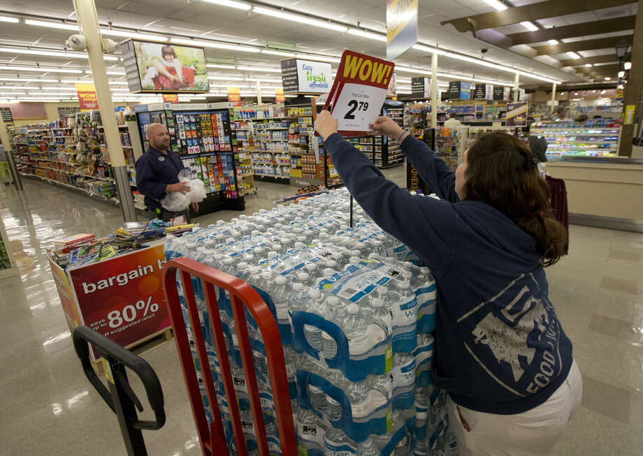Scan analyst Kristen Nice readies cases of bottled water for sale at the Food Lion in Newport News, Va., Thursday, Oct. 1, 2015, as the grocer brings in extra people for checkout and stocking as residents stock up on food essentials ahead of Hurricane Joaquin. (Adrin Snider/The Daily Press via AP) MANDATORY CREDIT (REV-SHARE) MBO